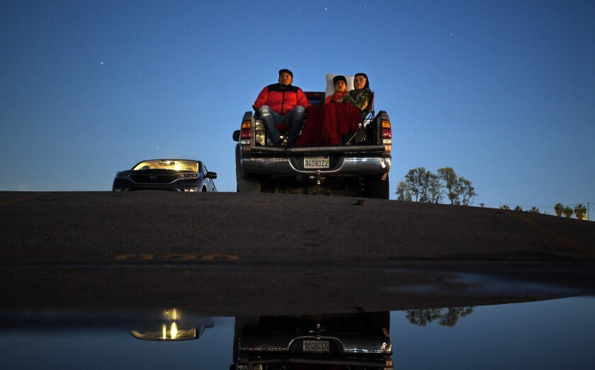 Sal Barbosa, left, Nathan Barbosa and DiAngelo Lujano watch a movie at Paramount Drive-In on Tuesday.