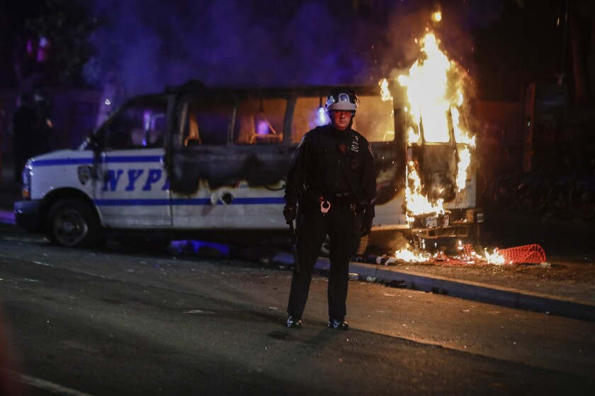 A police officer watches a crowd as a police vehicle burns near Fort Greene Park in the Brooklyn borough of New York
