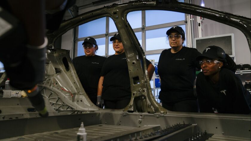 Tesla employees receive training on the general assembly of a Model 3 at the factory's training center in Fremont, Calif.