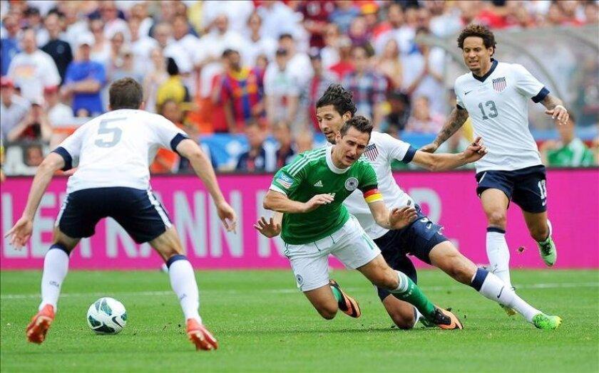Miroslav Klose (2i) de Alemania se enfrenta a  Omar Gonzalez (2d) de la selección de Estados Unidos en el partido amistoso entre los dos equipos disputado en el estadio Robert F. Kennedy Memorial en Washington, este domingo 2 de junio de 2013. EFE