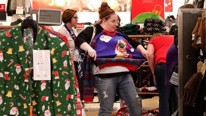 A Kohl's shopper in Crestwood, Mo., checks out a holiday sweater on Christmas Eve.