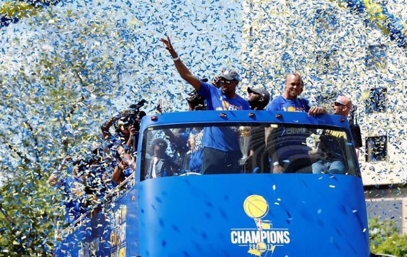 El jugador de Golden State Warriors Kevin Durant (i) saluda a la multitud junto a David West (d) durante el Desfile de los Campeones de la NBA el pasado mes de junio, en Oakland, California (EE.UU.). EFE/Archivo