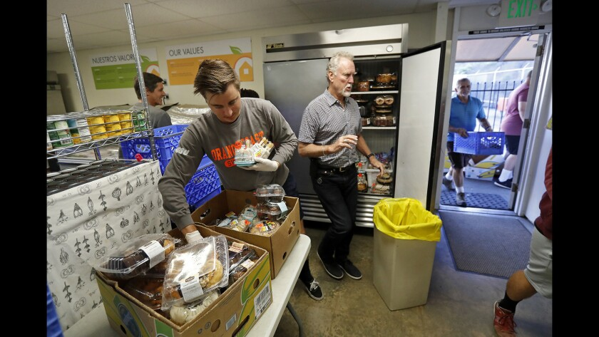 Volunteers stock food items at the Laguna Food Pantry in Laguna Beach on Friday.