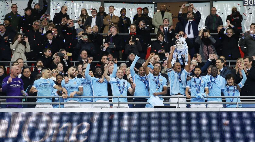 Manchester City's Vincent Kompany raises the trophy after winning the English League Cup final soccer match between Liverpool and Manchester City at Wembley stadium in London, Sunday, Feb. 28, 2016. (Sharon Latham/Pool via AP)