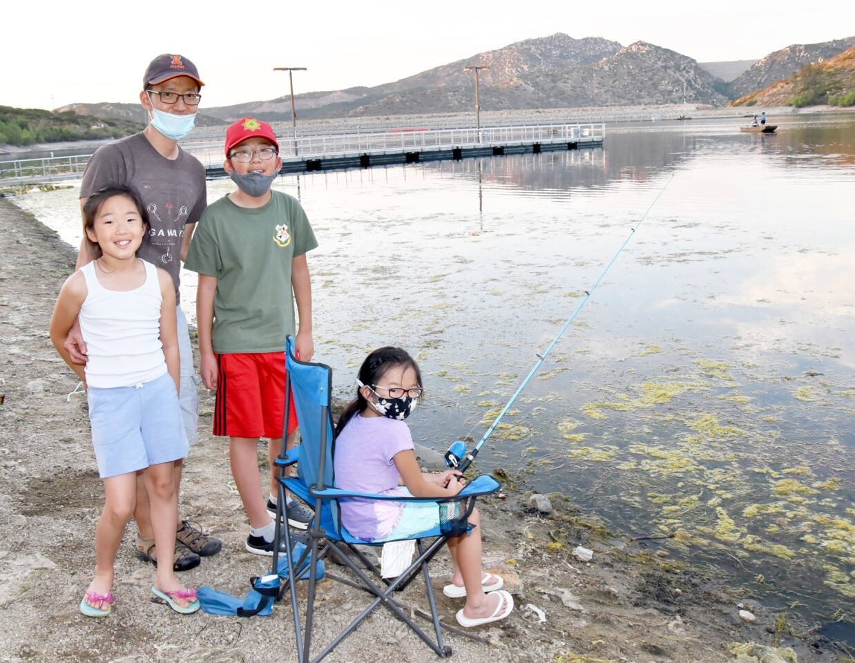 Taekjin Shin with his children, Norah, Nathan and Naomi, were among participants in the night fishing opportunity at Lake Poway on Saturday.