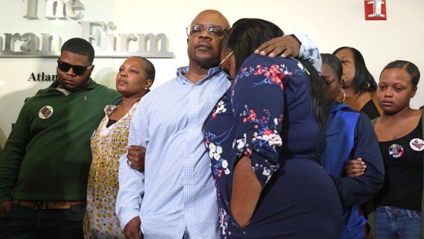 Charles Twyman, the father of Ryan Twyman, comforts his daughter Chiquita Twyman