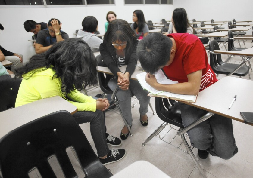 Students pray during InterVarsity Christian Fellowship meeting at Cal State Northridge. The group says it will not comply with a new systemwide policy mandating clubs to accept anyone as a group leader.
