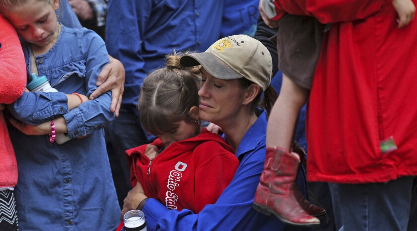 Becky Jones, center right, mourns during a candlelight vigil in Eden, Texas, on Tuesday, May 11, 2021, for her husband, Concho County sheriff's Deputy Stephen Jones, and fellow Deputy Samuel Leonard who were killed in the line of duty a day earlier. (Colin Murphey/The San Angelo Standard-Times via AP)