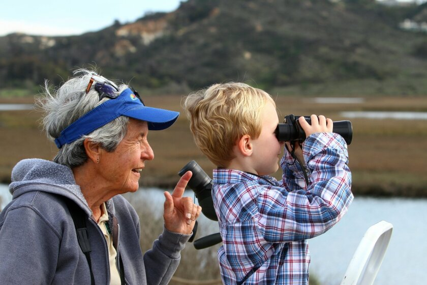 """Jarrett Cunningham, 5, observes an osprey sitting on a post with a fish with the help of San Elijo Lagoon Conservancy docent Elizabeth Vendrick during the """"Wings Over Wetlands"""" event Sunday at the lagoon."""