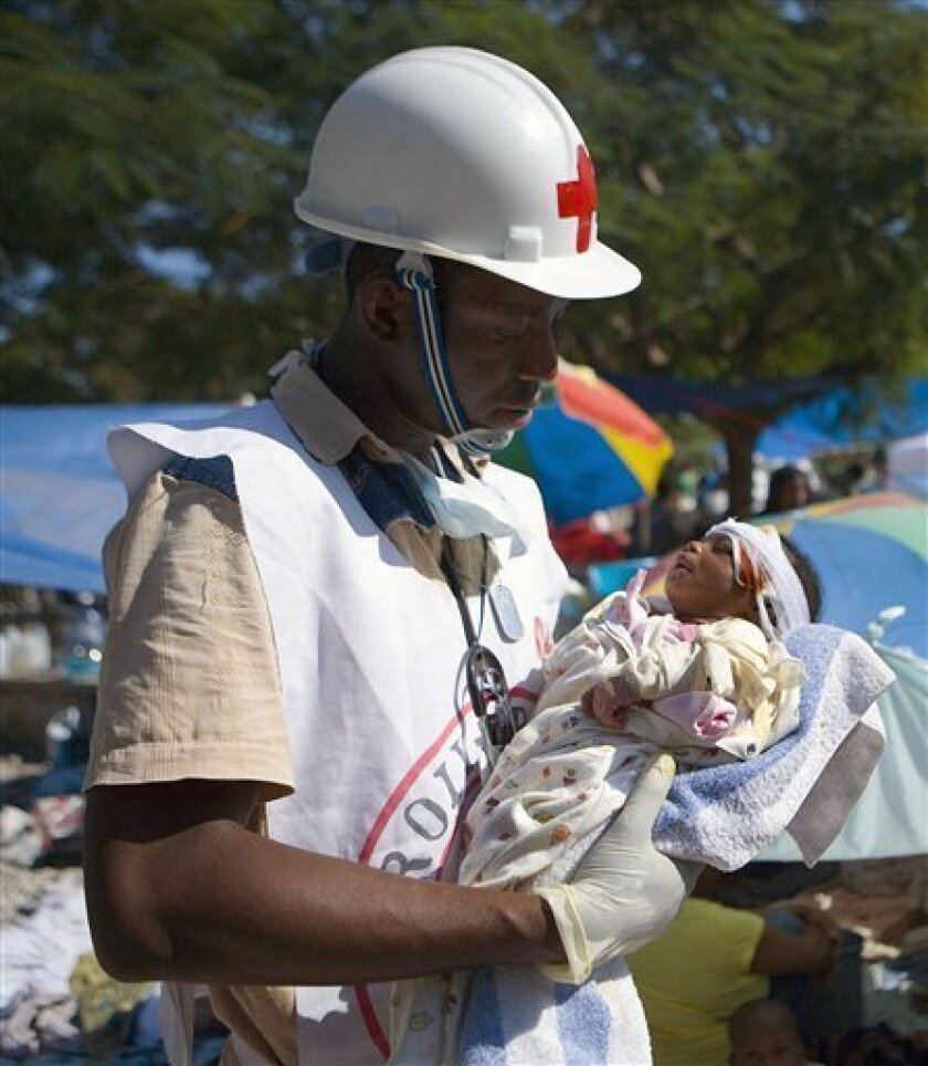 Red Cross volunteer Jean Zacharie delivers first aid to a 1-month old baby whose mother was killed by the earthquake, Friday, Jan. 15, 2010 in Port-au-Prince, Haiti Thousands of local Red Cross volunteers, many of whom were impacted by the earthquake, continue to provide first aid and distribute r