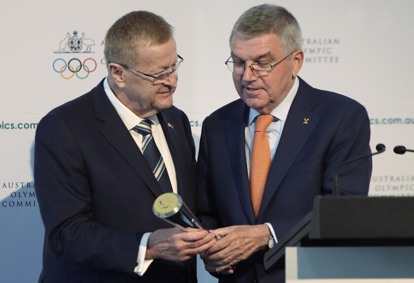 FILE - In this May 4, 2019, file photo, International Olympic Committee President Thomas Bach, right, is presented with the Australian Olympic Committee (AOC) President's trophy by AOC president John Coates at the AOC annual general meeting in Sydney, Australia. The only thing more difficult than staging next year's Tokyo Olympics in a pandemic might be convincing sponsors to keep their billions on board in the midst of economic turbulence and skepticism. (AP Photo/Rick Rycroft, File)