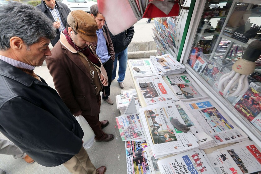 Iranians look at newspapers displayed outside a kiosk in Tehran after an interim deal was reached on the country's nuclear program.