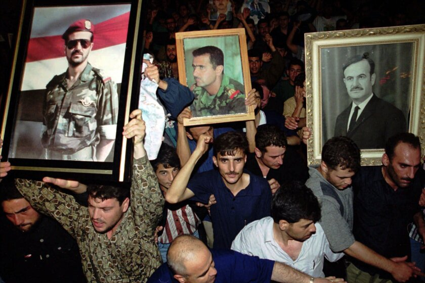 FILE - In this June 10, 2000 file photo, Syrian mourners wave portraits of President Hafez Assad, right, and his two sons Bashar, center, and Basil who died in a car accident in 1994 to mourn the death of their president, in Damascus, Syria. For fifty years, the Assad family has controlled Syria, overseeing transformations, modernization, uprisings and upheaval while becoming among the most divisive figures of their time. (AP Photo/Hussein Malla, File)