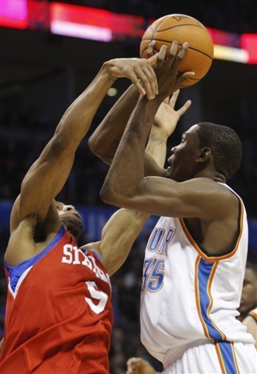 Oklahoma City Thunder forward Kevin Durant, right, is fouled by Philadelphia 76ers guard Andre Iguodala, left, as he shoots in the second quarter of an NBA basketball game in Oklahoma City, Wednesday, Dec. 2, 2009. (AP Photo/Sue Ogrocki)