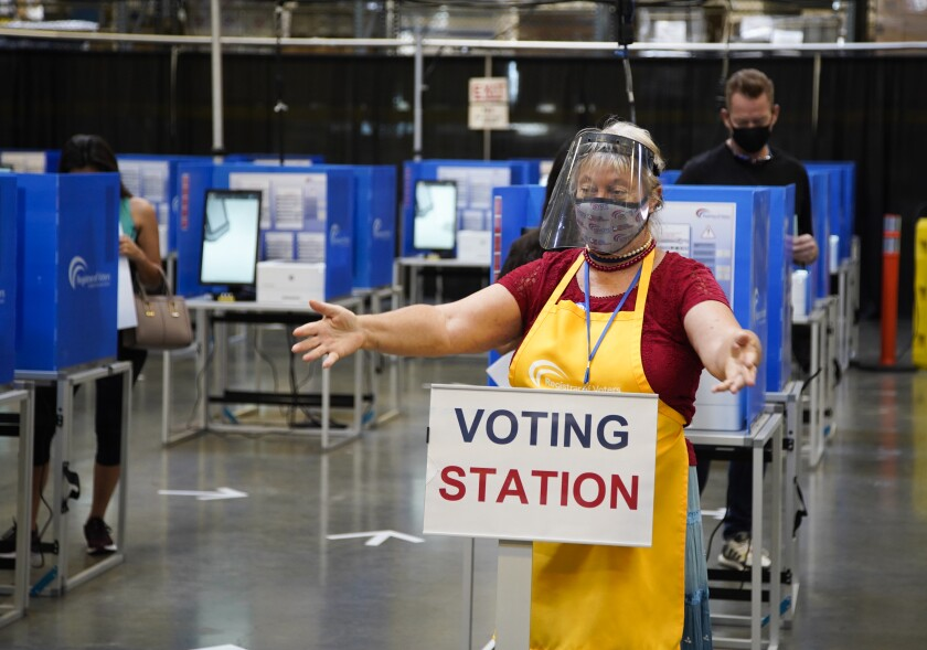 Poll worker assisting voters to the correct station.