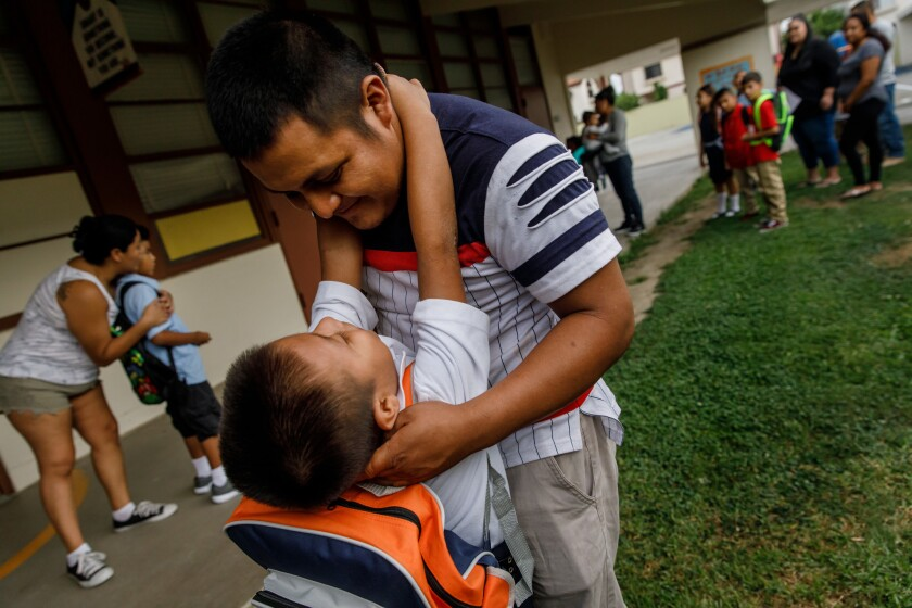 Jefferson Che Pop embraces his father, Hermelindo Che Coc, on the first day of school.