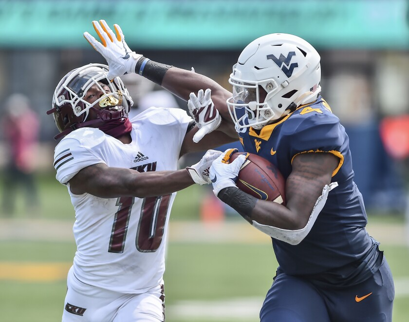 West Virginia running back Leddie Brown (4) stiff arms Eastern Kentucky's Davion Ross (10) during an NCAA college football game on Saturday, Sept. 12, 2020, in Morgantown, W.Va. (William Wotring/The Dominion-Post via AP)