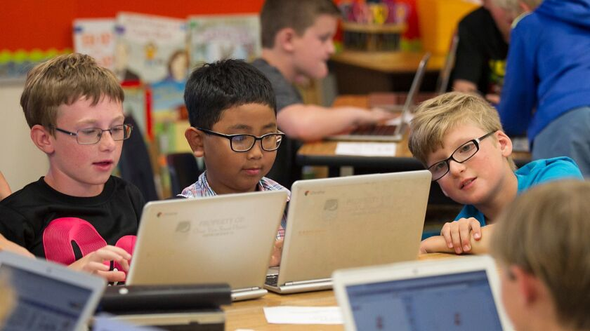 Students Paul Young, David Tran and Nolan Neves, from left, work during a computer programming after-school course at Circle View Elementary School in Huntington Beach.