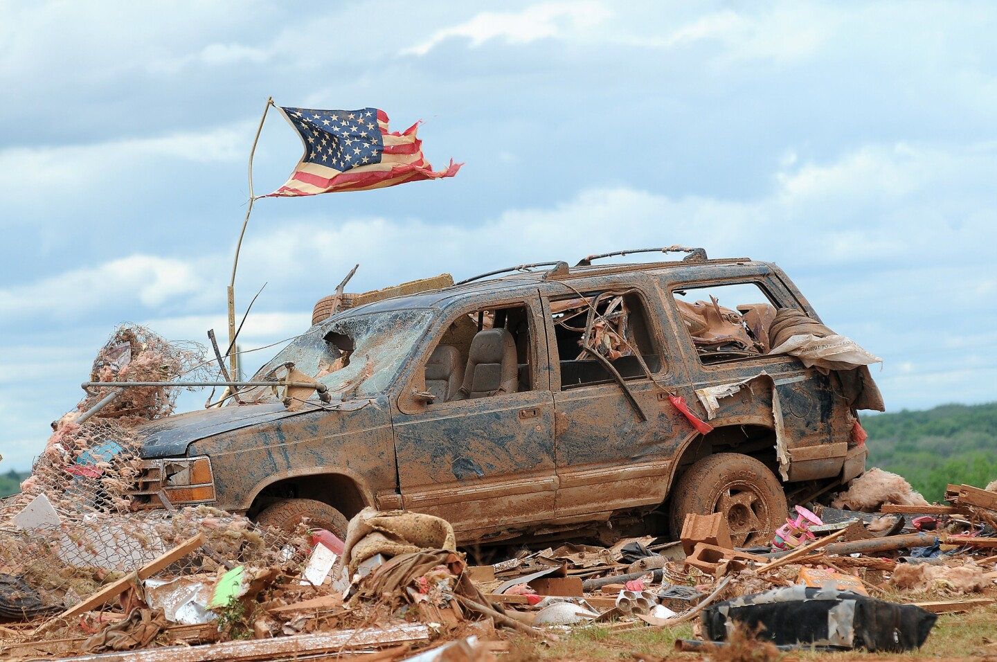 A tattered American flag flies over a vehicle where two girls, 5 and 7, were found dead after a severe thunderstorm spawned a massive tornado at Hideaway Mobile Home Villa in Woodward, Okla. Residents of several states scoured through the wreckage of battered homes and businesses Sunday, after dozens of tornadoes blitzed the Midwest and Plains Saturday, leaving six dead and 29 injured.