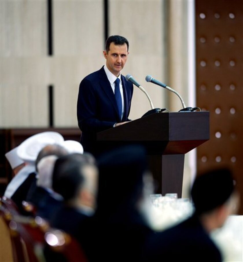 In this Sunday, Aug. 4, 2013 photo released by the Syrian official news agency SANA, Syrian President Bashar Assad delivers a speech at an Iftar dinner with political and religious figures in Damascus, Syria. (AP Photo/SANA)