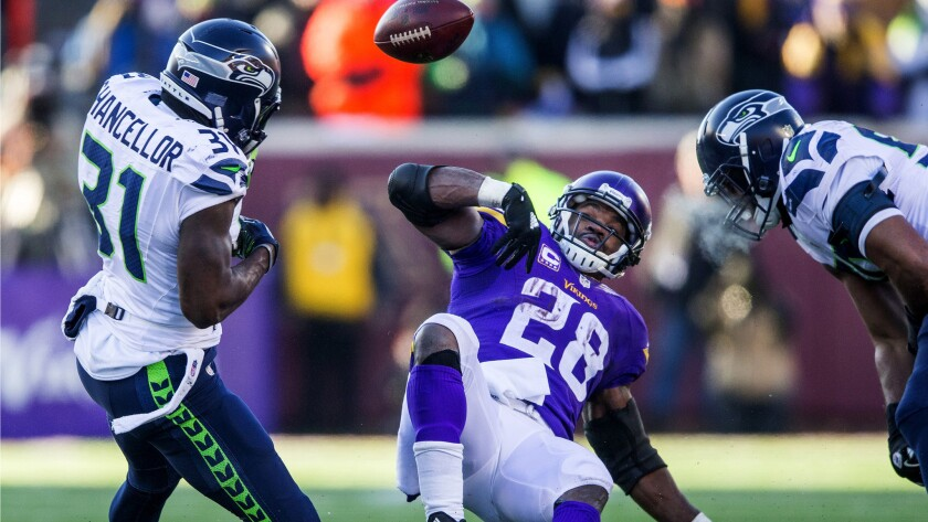 Seahawks safety Kam Chancellor (31) strips the ball from Vikings running back Adrian Peterson during a key fourth-quarter play Sunday.