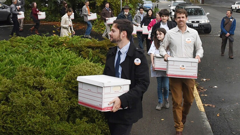 Carbon Washington campaign organizer Ben Silesky leads a group of supporters into the elections office for the Washington secretary of State.