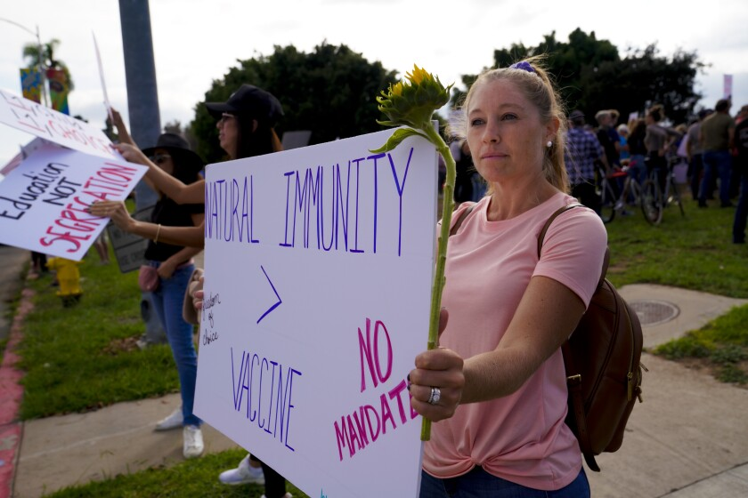Alyssa Titus was held up a sign objecting to mandatory vaccinations while at San Diego Unified headquarters  Tuesday.