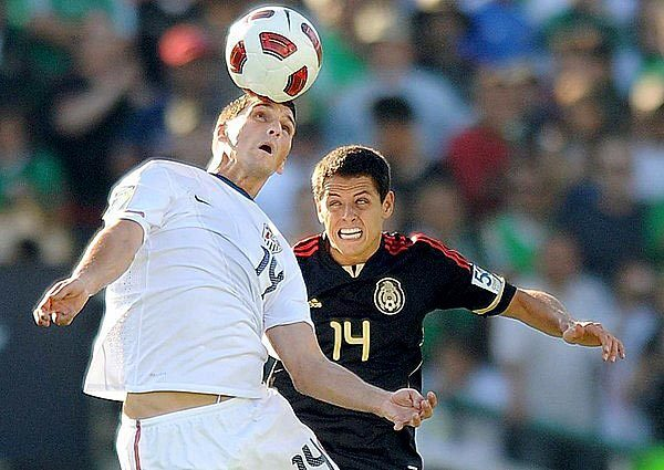 U.S. defender Eric Lichaj heads the ball away from Mexico forward Javier Hernandez in the first half of the Gold Cup final on Saturday evening at the Rose Bowl.
