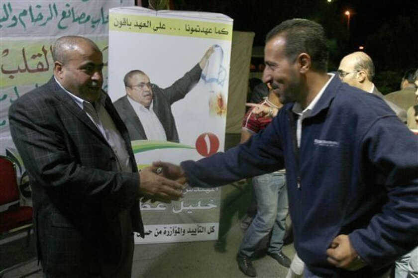 In this photo Taken on Wednesday, Nov.3, 2010, Jordanian candidate for the parliamentary election Khalil Atiyeh, left, receives one of his supporters with a poster behind him shows him burning the Israeli flag, at his electroal headqurter in Amman, Jordan. Election time in Jordan is raising fears yet again of another mass exodus of Palestinian refugees from the West Bank should peacemaking with Israel flounder.(AP Photo/Nader Daoud)