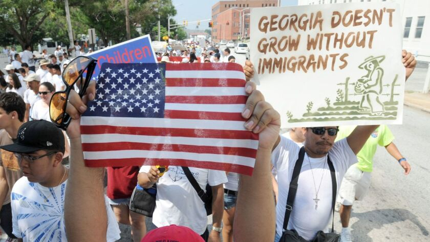 A man holds a United States flag while marching through downtown Atlanta in protest against a Georgia immigration law on July 2, 2011.