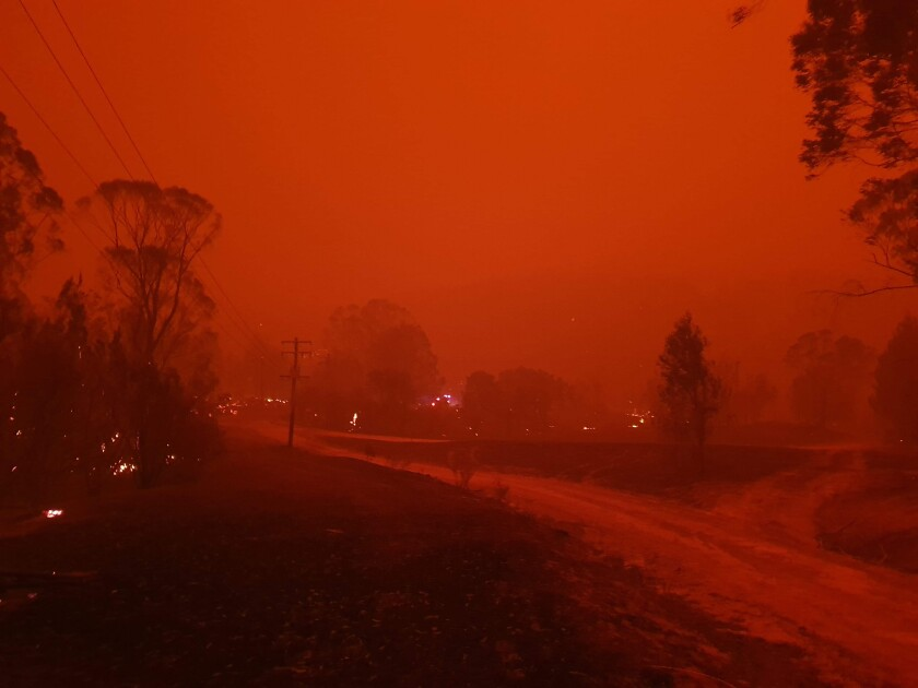 In this Dec. 31, 2019, photo provided by Siobhan Threlfall, fire and thick smoke remains the village of Nerrigundah, Australia. The tiny village has been among the hardest hit by Australia's devastating wildfires, with about two thirds of the homes destroyed and a 71-year-old man killed. (AP Photo/Siobhan Threlfall)
