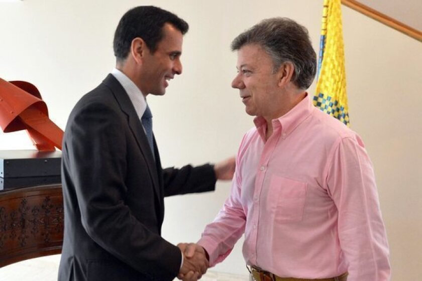 Colombian President Juan Manuel Santos, right, greets Venezuelan opposition politician Henrique Capriles at the presidential palace in Bogota.