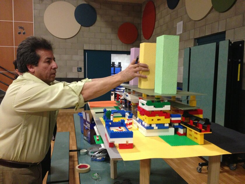 Miguel Aguirre puts the finishing touches on his Lego model of what he thinks the new San Ysidro Intermodal Transportation Center should look like.