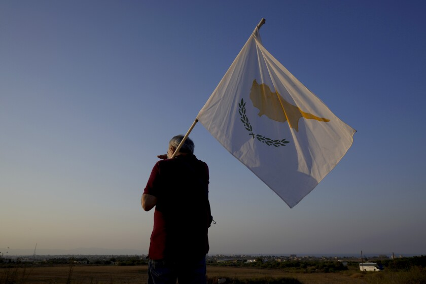 A man with a Cyprus flag stands in front of the Varosha or Famagusta, abandoned city, during a protest against the Turkish President visiting the Turkish occupied part of the island at the north and the 47th anniversary against the Turkish invasion in the island, in Dherynia, Cyprus, Monday, July 19, 2021. The only route to lasting peace on ethnically divided Cyprus is through the international community's acceptance of two separate states on the east Mediterranean island nation, Turkey's president said. (AP Photo/Petros Karadjias)