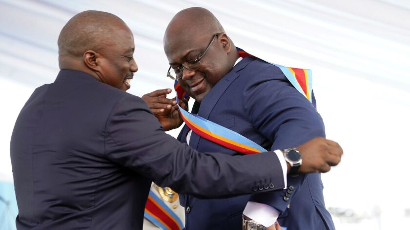 Congolese President Felix Tshisekedi, right, receives the presidential sash from outgoing president