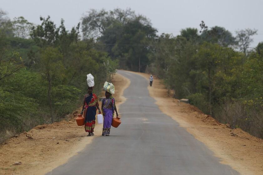 Aldeanos indios caminan hacia su aldea en las afueras de Hyderabad, India, viernes 26 de febrero de 2021. (AP Foto/Mahesh Kumar A.)