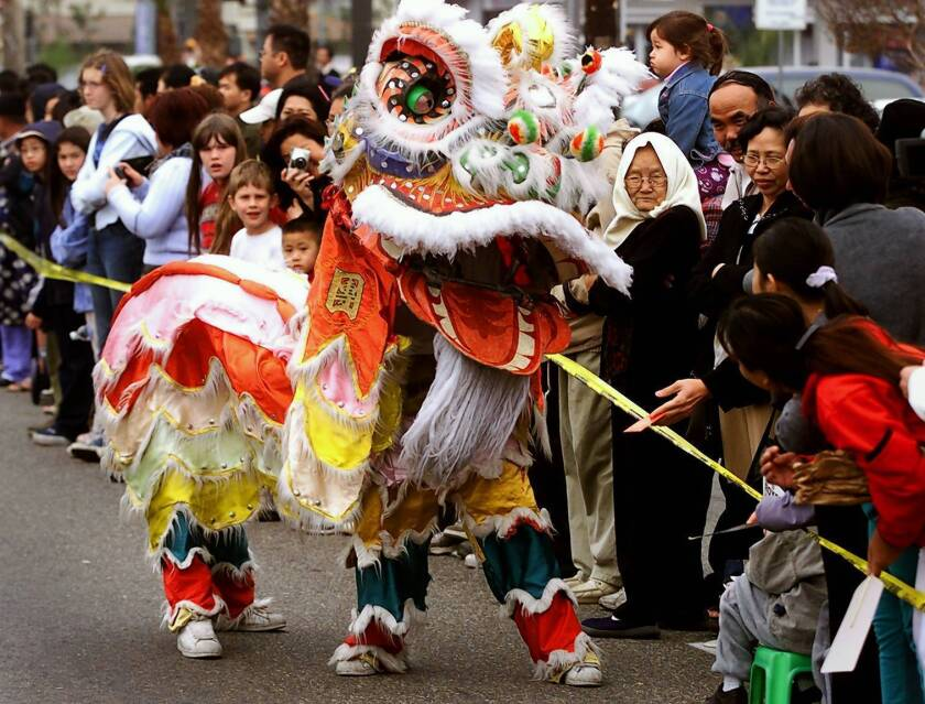The crowd along Bolsa Ave. interacts with dragon dancers during a previous Tet Parade in Westminster.
