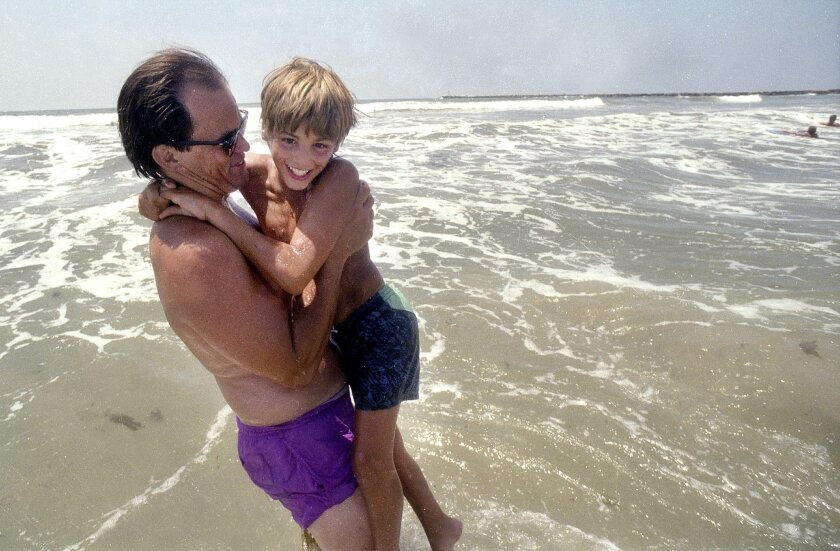 Danny Ruckel holds adopted son Izidor Ruckel, 11, at San Diego's Ocean Beach in 1992 after the Ruckel family adopted Izidor from his home country of Romania.  Young Izidor was often consumed with thoughts of the other orphans he left and now at the age of 33, is telling their story.