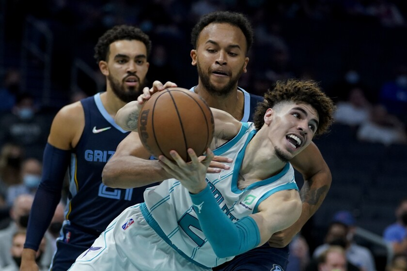 Charlotte Hornets guard LaMelo Ball works around Memphis Grizzlies forward Kyle Anderson during the second half of a preseason NBA basketball game on Thursday, Oct. 7, 2021, in Charlotte, N.C. (AP Photo/Chris Carlson)