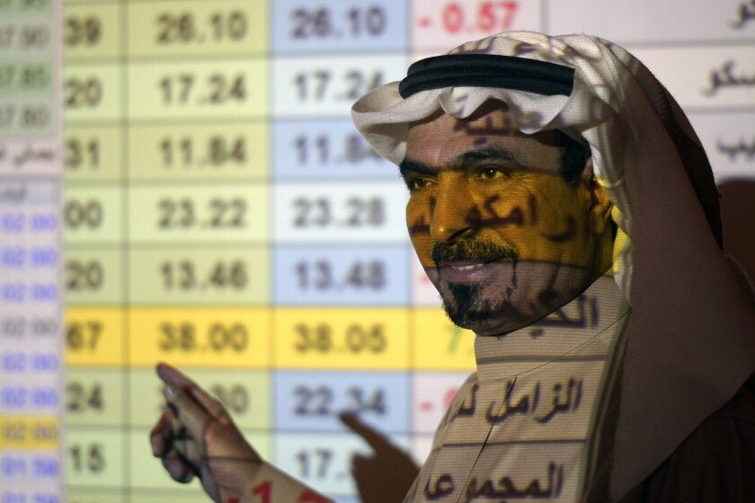 A Saudi trader stands in front of a screen displaying the Saudi stock market Dec. 12 at the Arab National Bank in Riyadh.