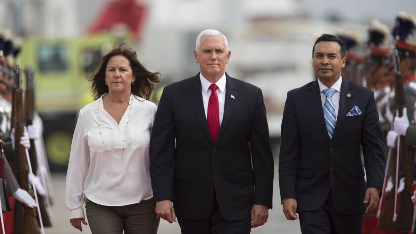 U.S. Vice President Mike Pence and wife Karen are escorted by Guatemalan Vice Foreign Minister Pablo Garcia, right, on arrival at an air base in Guatemala City on June 28, 2018.