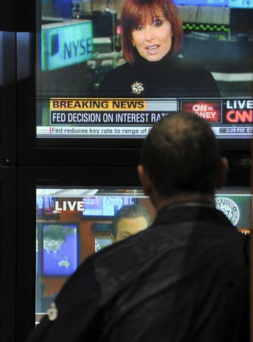 A New York Stock Exchange specialist watches a TV report on the Federal Reserve's decision to lower the short-term lending rate to near zero In December 2008.