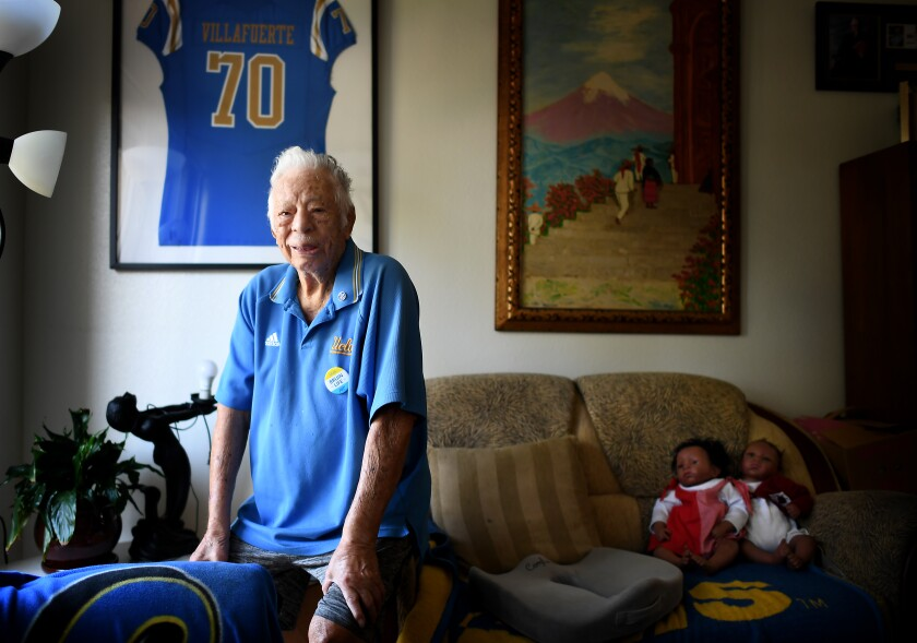UCLA fan George Villafuerte sits in the living room of his apartment in Reseda.