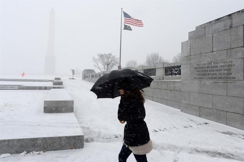 Una mujer visita el Monumento nacional a la Segunda Guerra Mundial durante una tormenta de nieve en Washington D.C. (EEUU). EFE/Archivo