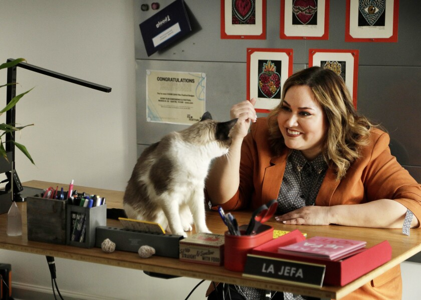 LOS ANGELES, CA -- MAY 14, 2019: Tanya Saracho, sharing her desk with her cat Roscoe, serves as the