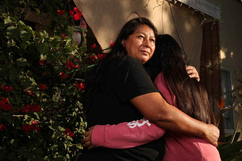 A mother hugs her 13-year-old daughter outside their home