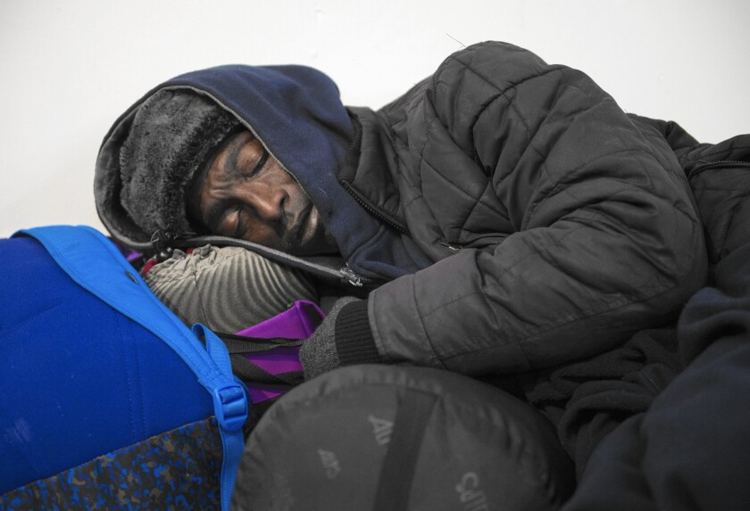 Derrick Hunter sleeps while waiting to be bused to a church to spend the night out of the cold in Sacramento. The cold system was expected to weaken.