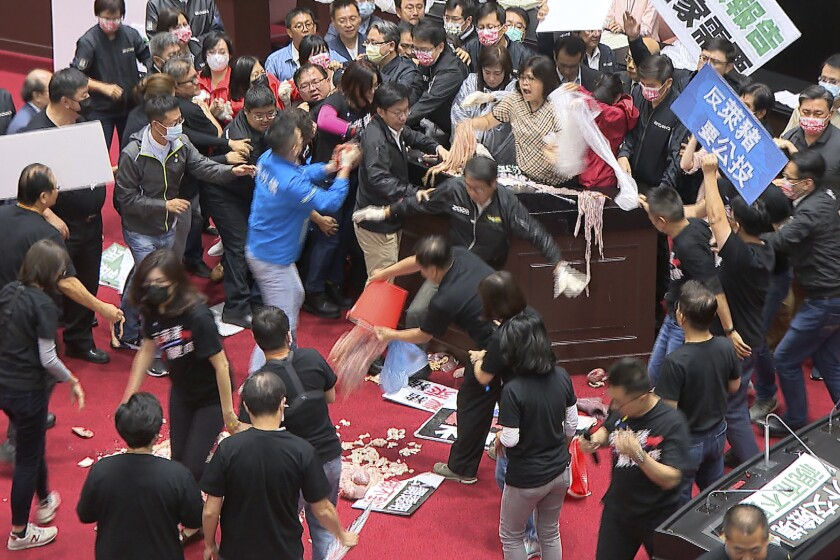 """In this image made from video, lawmakers fight during a parliament session in Taipei, Taiwan, Friday, Nov. 27, 2020. Taiwan's lawmakers got into a fist fight and threw pig guts at each other Friday over a soon-to-be enacted policy that would allow imports of U.S. pork and beef. A blue banner at right reads: """"Protest against ractopamine pork, We want a referendum."""" (FTV via AP)"""