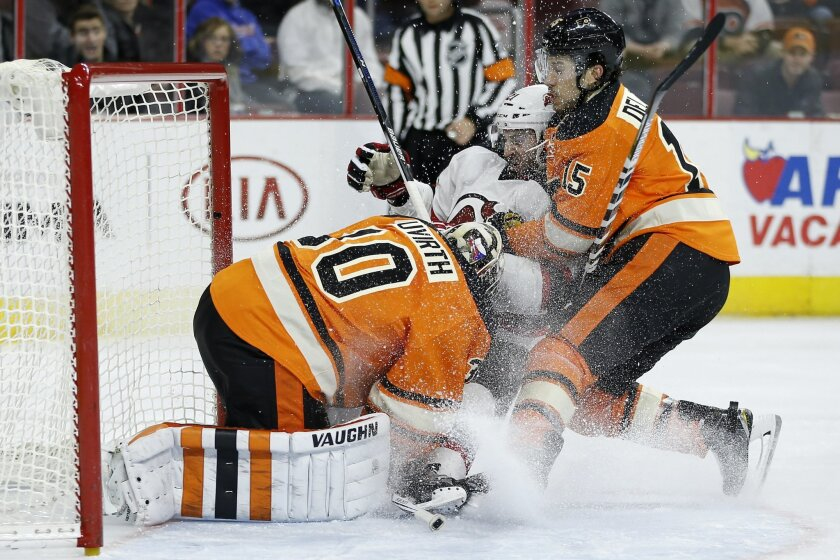 Philadelphia Flyers' Michael Del Zotto, right, and New Jersey Devils' Kyle Palmieri, center, collide with goalie Michal Neuvirth during the third period of an NHL hockey game, Saturday, Feb. 13, 2016, in Philadelphia. New Jersey won 2-1 in overtime. (AP Photo/Matt Slocum)