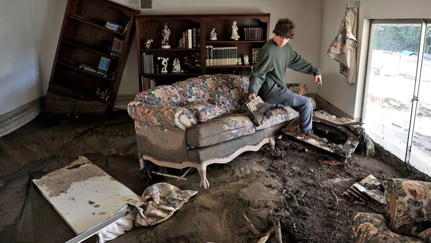 A resident who chose not to give his name surveys the damage at a home on Manistee Dr., after a mud